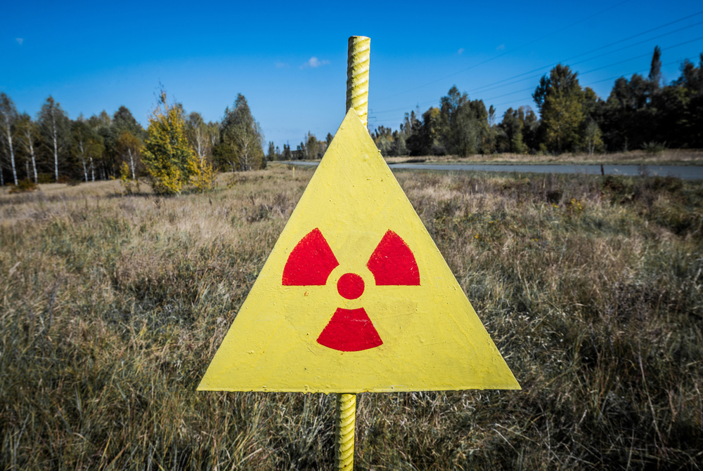 Ionizing Radiation sign next to Red Forest in Chernobyl Nuclear Power Plant Zone of Alienation, Ukraine: Chernobyl Wolves
